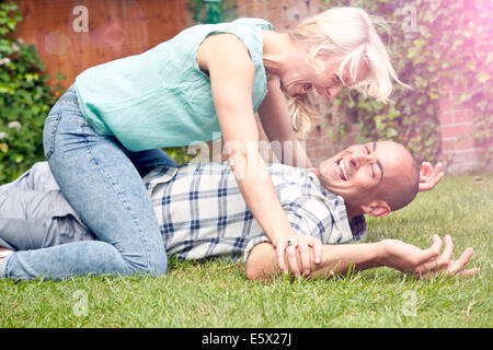 Happy couple play fighting in garden - Stock Photo