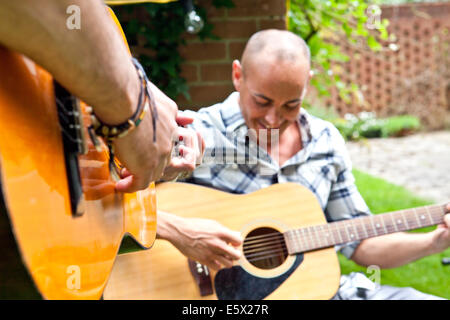 Cropped shot of two male friends playing acoustic guitar in garden - Stock Photo