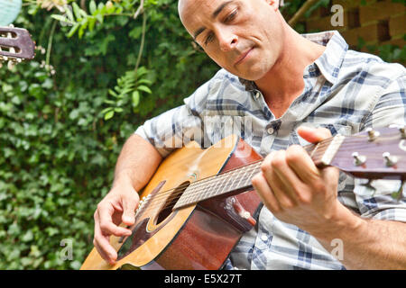 Mid adult man playing acoustic guitar in garden - Stock Photo