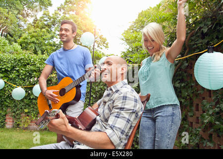 Male friends playing acoustic guitar in garden and young woman dancing - Stock Photo