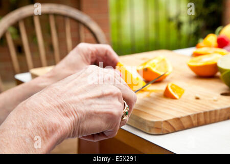 Hands of senior woman slicing oranges at garden table - Stock Photo