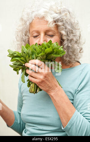 Mature woman smelling bunch of mint in garden - Stock Photo