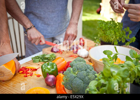 Cropped shot of three male friends preparing food for garden barbecue - Stock Photo
