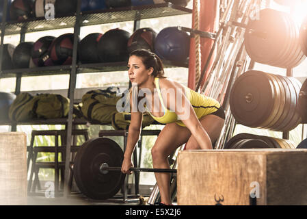Bodybuilder bending to lift barbell in gym - Stock Photo