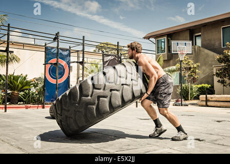 Man lifting huge wheel in basketball court - Stock Photo