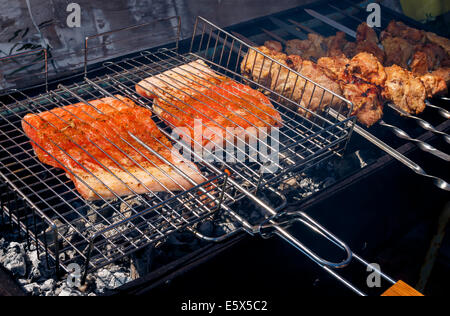 meat and fish kebabs grilling at nature, pork or lamb and salmon - Stock Photo