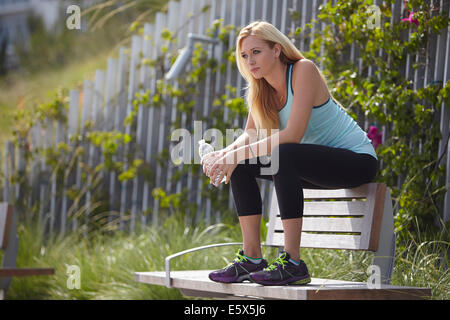 Woman sitting on top of park bench - Stock Photo