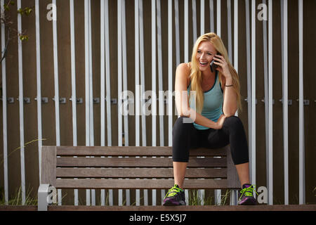 Woman chatting on smartphone on park bench - Stock Photo