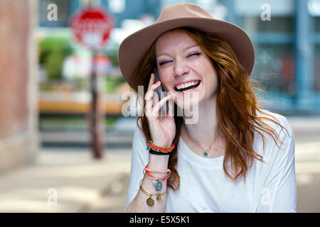 Portrait of young woman using mobile phone - Stock Photo