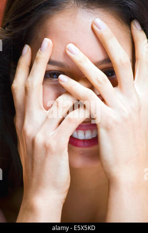 Portrait of young woman with hands covering face - Stock Photo