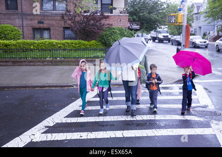 Children go home after school on a rainy day in Brooklyn, NY. - Stock Photo