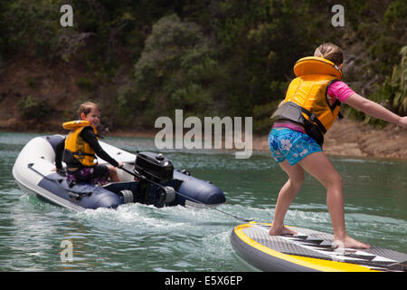 Brother in motor dinghy towing sister standing on paddleboard