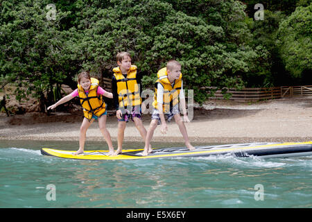 Brothers and sister standing on paddleboard at sea
