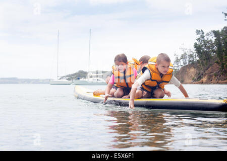 Brothers and sister paddleboarding on knees at sea