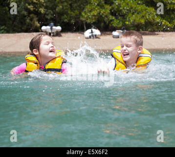 Brother and sister play fighting and splashing in sea - Stock Photo