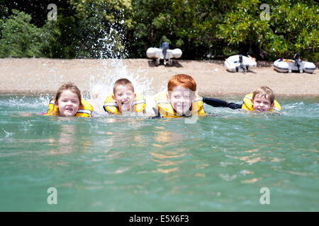 Brothers and sister in a row swimming in sea - Stock Photo