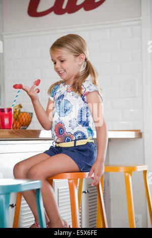 Girl sitting on kitchen stool with raspberries on her fingers - Stock Photo