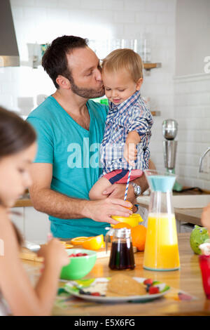 Mid adult man multi tasking breakfast with son and daughter - Stock Photo