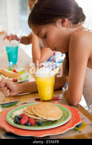Two sisters blowing bubbles through straws at breakfast bar - Stock Photo
