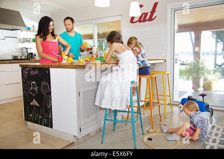 Mid adult parents and three children preparing breakfast in kitchen - Stock Photo