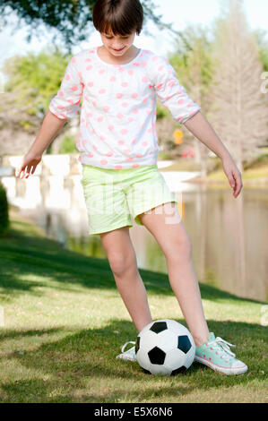 Ten year old girl playing with soccer ball in park - Stock Photo