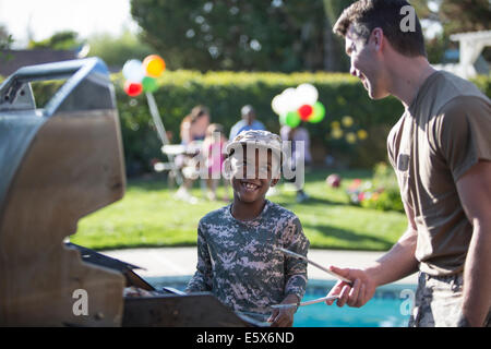 Male soldier and boy barbecuing at homecoming party - Stock Photo