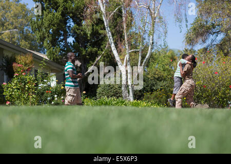 Female soldier hugging son in garden on homecoming - Stock Photo