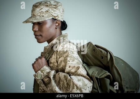 Side view studio portrait of female soldier with rucksack looking down - Stock Photo