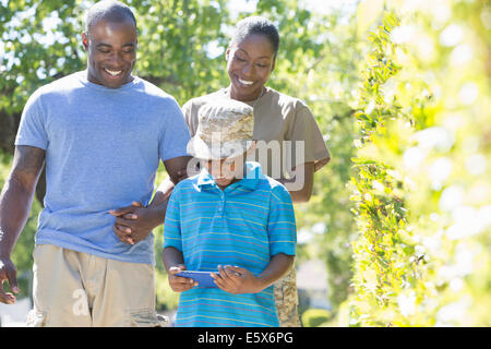 Female soldier strolling with family on homecoming - Stock Photo