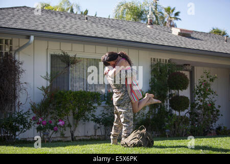 Male soldier hugging and lifting wife in garden on homecoming - Stock Photo