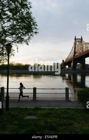 Silhouette of young woman running on waterfront, Roosevelt Island, New York City, USA - Stock Photo