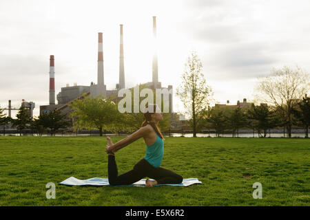Young woman practicing yoga in city park at sunrise - Stock Photo