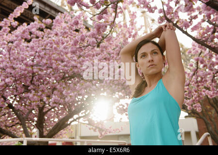 Young female runner stretching and warming up in city park - Stock Photo
