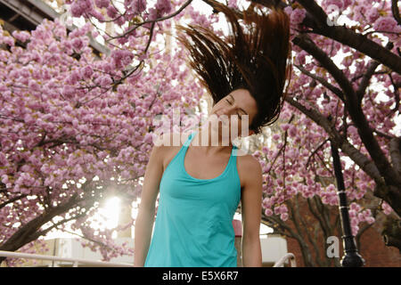 Young female runner warming up in city park - Stock Photo