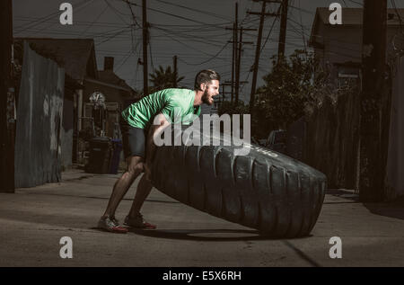 Young adult man lifting large tire - Stock Photo