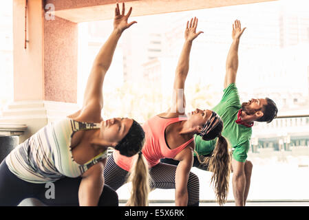 Group of young adults doing yoga - Stock Photo