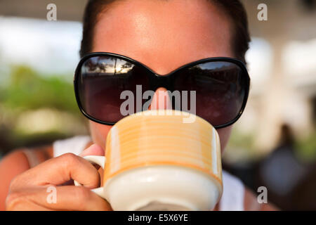 Close up of mid adult woman in sunglasses drinking from coffee cup - Stock Photo