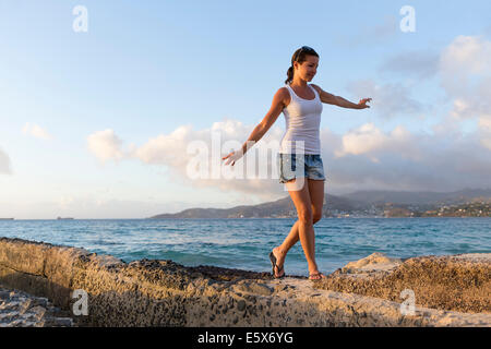 Mid adult woman walking along pier, Spice Island beach resort, Grenada, Caribbean - Stock Photo
