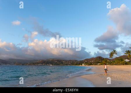 Rear view of mid adult woman strolling on beach, Spice Island beach resort, Grenada, Caribbean - Stock Photo
