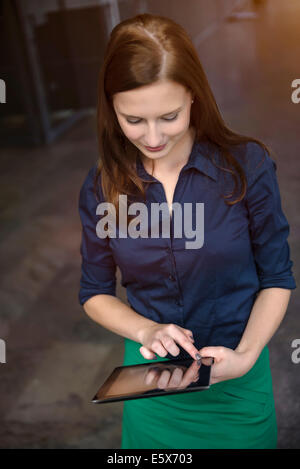 Young businesswoman using digital tablet in office - Stock Photo