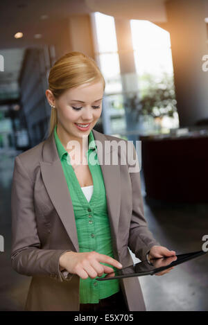 Young businesswoman using touchscreen on digital tablet in office - Stock Photo