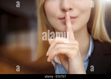 Close up cropped image of young businesswoman with finger on lips - Stock Photo