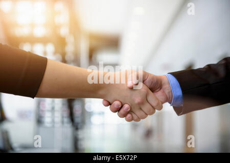Close up of businesswomen and businessman shaking hands in office - Stock Photo