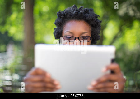 Young woman in park holding up and reading digital tablet - Stock Photo