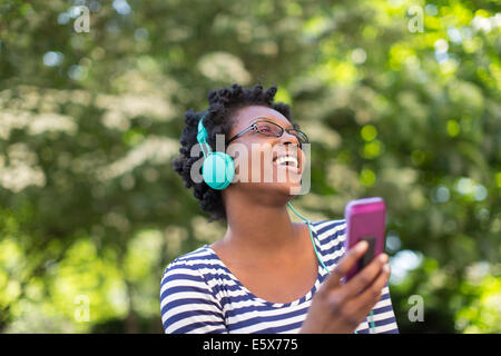 Young woman in park listening and singing to music on headphones - Stock Photo