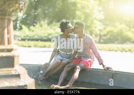 Young couple kissing with bare feet in Bethesda fountain, Central Park, New York City, USA - Stock Photo