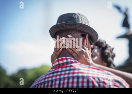 Close up of young couple kissing next to Bethesda fountain, Central Park, New York City, USA - Stock Photo
