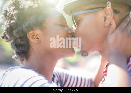 Close up of young couple kissing in park - Stock Photo