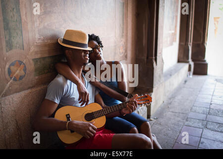 Young couple sitting with mandolin in Bethesda Terrace arcade, Central Park, New York City, USA - Stock Photo