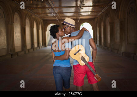 Rear view of young couple with mandolin in Bethesda Terrace arcade, Central Park, New York City, USA - Stock Photo